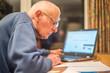 canvas print picture - Elderly man using a laptop computer to check share portfolios ,Hampshire,England,U.K.