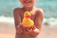 Little Girl Holding In Hands Yellow Rubber Duck Toy On The Beach