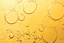 Beautiful Macro Photo Of Water Droplets In Oil With A Yellow Background.