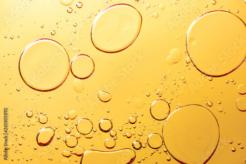 Fototapeta Beautiful macro photo of water droplets in oil with a yellow background. obraz