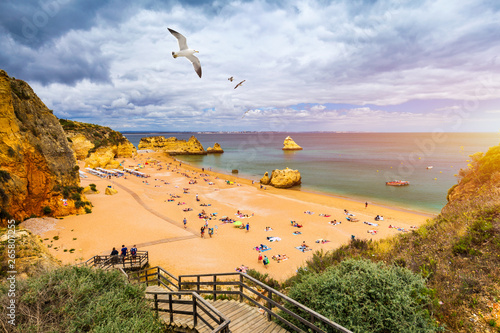 Wooden walkway to famous Praia Dona Ana beach with turquoise sea water and cliffs, flying seagulls over the beach, Portugal Canvas Print