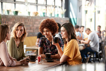 Four Young Female Friends Meeting Sit At Table In Coffee Shop And Talk