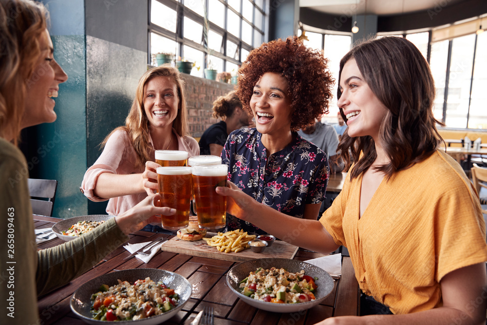 Fototapety, obrazy: Four Young Female Friends Meeting For Drinks And Food Making A Toast In Restaurant