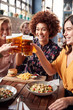 canvas print picture - Four Young Female Friends Meeting For Drinks And Food Making A Toast In Restaurant