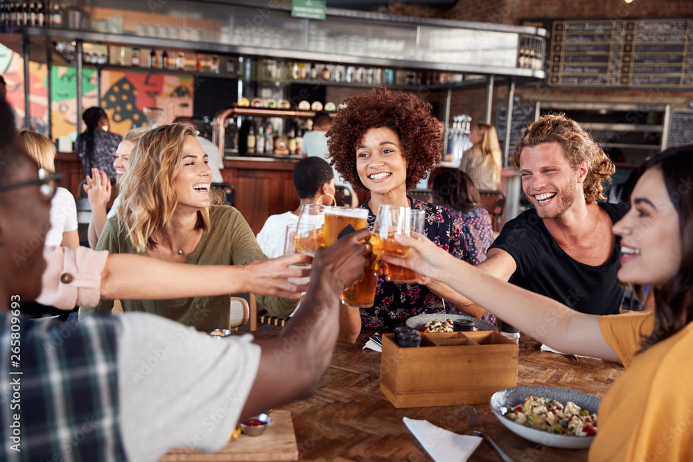 Fototapety, obrazy: Group Of Young Friends Meeting For Drinks And Food Making A Toast In Restaurant