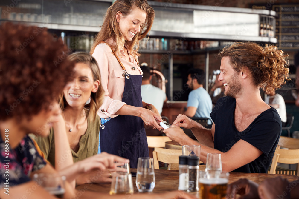 Fototapety, obrazy: Waitress Holds Credit Card Machine As Customer Pays Bill In Bar Restaurant