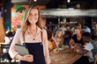 canvas print picture Portrait Of Waitress Holding Menus Serving In Busy Bar Restaurant