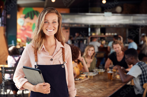 Poster Restaurant Portrait Of Waitress Holding Menus Serving In Busy Bar Restaurant