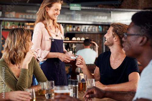 Fényképezés  Waitress Holds Credit Card Machine As Customer Pays Bill In Bar Restaurant