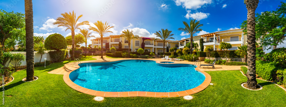 Fototapety, obrazy: Great backyard with swimming pool, hot tub and lounge chairs. Swimming pool in backyard. Incredible swimming pool and garden with palm trees and flowers in a sunny day.