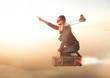 Mutige Entdeckerin fliegt auf Ihrem Koffer Richtung Sonnenaufgang in den Urlaub