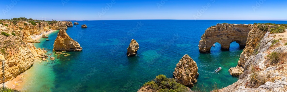 Fototapety, obrazy: Natural caves at Marinha beach, Algarve Portugal. Rock cliff arches on Marinha beach and turquoise sea water on coast of Portugal in Algarve region.
