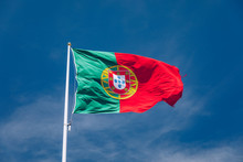 Beautiful Large Portuguese Flag Waving In The Wind Against Blue Sky. Portuguese Flag Waving Against Blue Sky. Flag Of Portugal Waving, Against Blue Sky