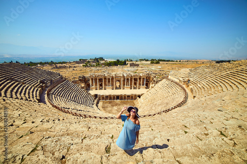 Woman traveler in hat looking at amazing Amphitheater ruins in ancient Hierapolis, Pamukkale, Turkey. Grand panoramic view