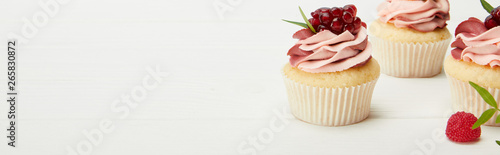 Photo  panoramic shot of sweet cupcakes with garnet on white surface