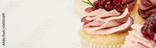 Photo  panoramic shot of cupcakes with cream and garnet isolated on white