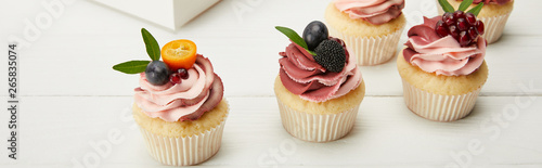 Photo  panoramic shot of cupcakes with fruits and berries on white surface