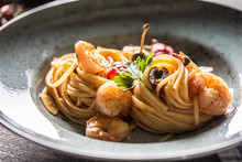Pasta Spaghetti On Plate And Pan With Shrimp Tomato Sauce Toatoes And Herbs. Italian Or Mediterranean Cuisine
