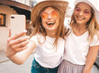 canvas print picture - Two young smiling hipster blond women in summer white t-shirt clothes. Girls taking selfie self portrait photos on smartphone.Models posing on street background.Female showing positive face emotions