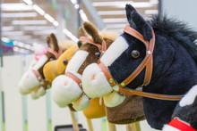Row Of Multicolored Hobbyhorses - Children Toys.