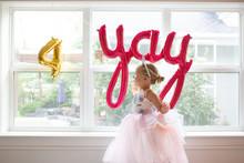 Side View Of Cute Girl In Fancy Dress By Window For Birthday