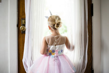 Small Blonde Girl With Unicorn Headband Looking Out Front Door