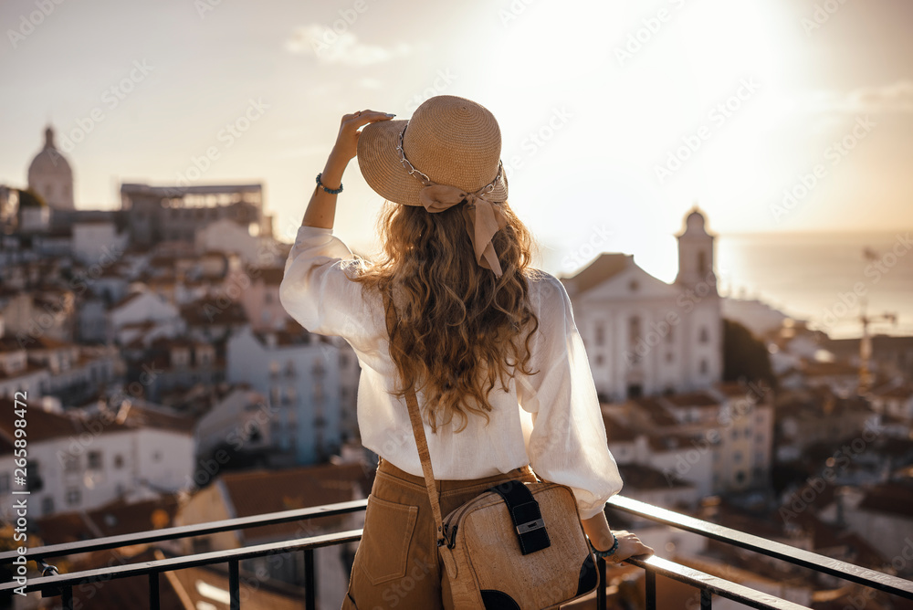 Fototapeta Blonde woman standing on the balcony and looking at coast view of the southern european city with sea during the sunset, wearing hat, cork bag, safari shorts and white shirt
