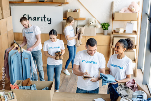 young, cheerful multicultural volunteers in white t-shirts with volunteer inscri Canvas Print