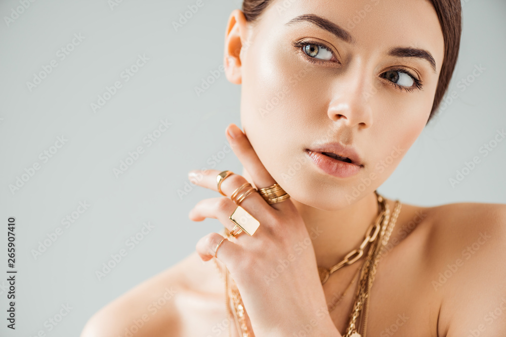 Fototapeta young nude woman in golden rings and necklaces looking away isolated on grey