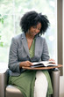 Black African American female as an adult student reading a book in a classroom or college campus.  The woman has an educational textbook or a novel or encyclopedia or bible.