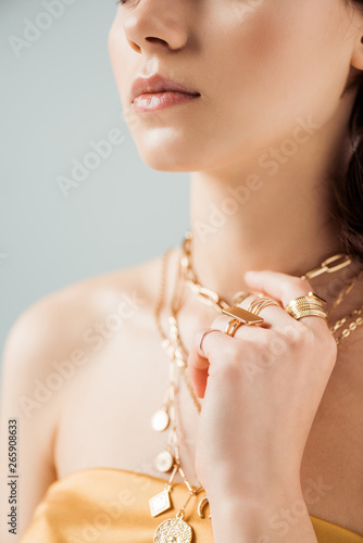 Foto partial view of young woman with shiny lips in golden necklaces and rings isolat
