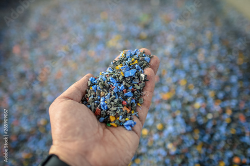 Fotografia Hand holding recycled plastic chips as raw material in production