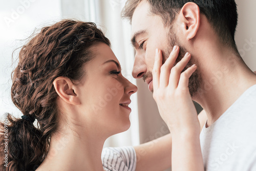 Fotomural happy smiling woman stroking bearded boyfriend at home