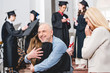 back view of girl in graduation cap hugging with father near crying mother