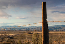 Rusty Barbed Wire Fence Against Western Backdrop In South Boise, Idaho