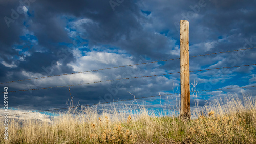 Rusty barbed wire fence against western skies in the American West Wallpaper Mural