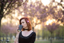 Drinking Coffee From Paper Mug Cup - Happy Young Travel Dancer Woman Enjoying Free Time In A Sakura Cherry Blossom Park - Caucasian White Redhead Girl