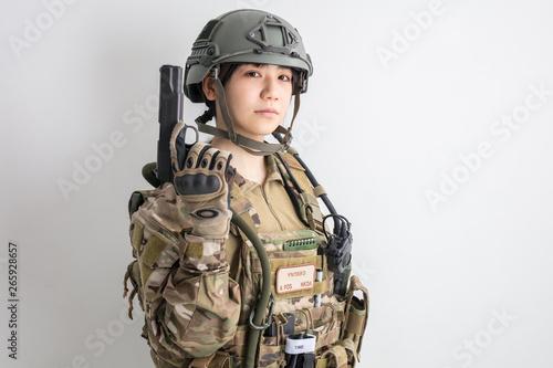 Photo 白背景に迷彩服を全身着たかっこいい女の子が銃を持っているサバイバルゲームサバゲー体験