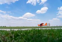 Small Red Charter Airplane Waiting On A Green Field To Take Off