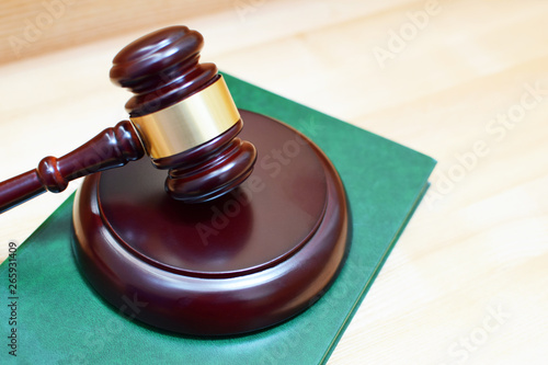 Photo Judges gavel or mallet on green law book on wooden table