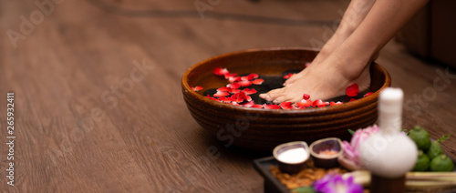 Photo sur Toile Pedicure Closeup shot of a woman feet dipped in water with petals in a wooden bowl