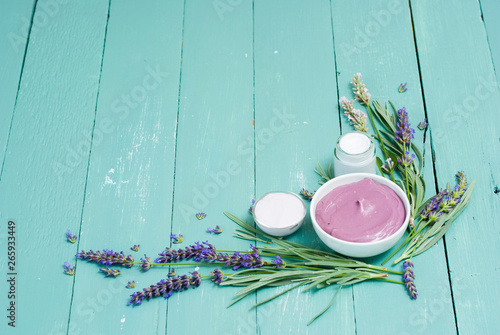 cosmetic creams and lavender flowers on blue wooden table