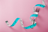 Fototapeta Coffie - Fork with measuring tape around on pink background