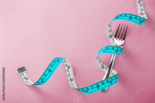 Photo  Fork with measuring tape around on pink background