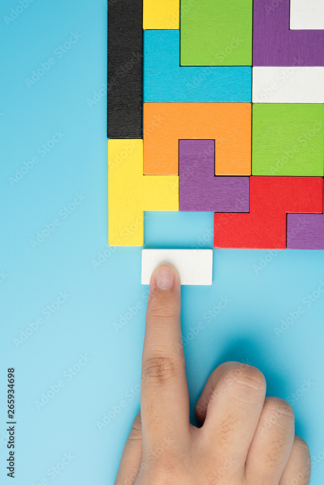 Fototapeta Hand push last piece jigsawto finish success planning concept solve puzzle isolated on blue background top view , logical thinking