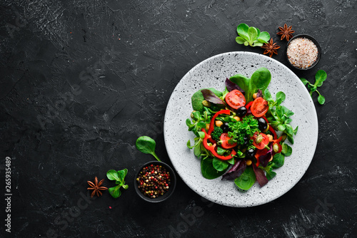 Photo  Vegetable salad with spinach, tomatoes, paprika and pumpkin seeds in a plate on a wooden background Top view