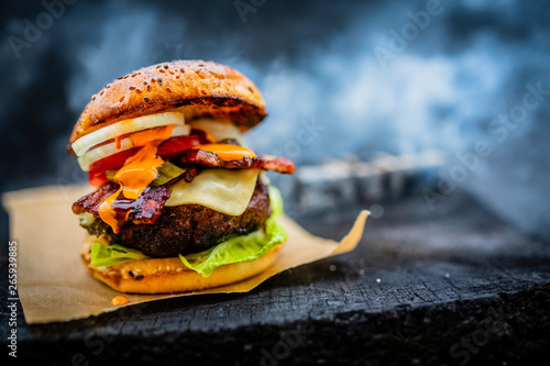 Fototapeta Tasty smoked grilled and glazed beef burger with lettuce, cheese and bacon served with french fries on wooden table with copyspace, smoke mesquite timber wood in background. obraz