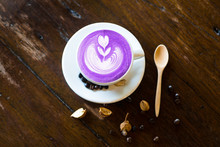 Taro Latte Art With Coffee Bean And Wood Spoon On Wood Table