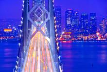 View Of Bay Bridge Across San Francisco Bay With Lots Of Cars Passing Through In San Francisco At Night.