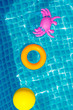 Inflatable toys floating in swimming pool on sunny day, top view